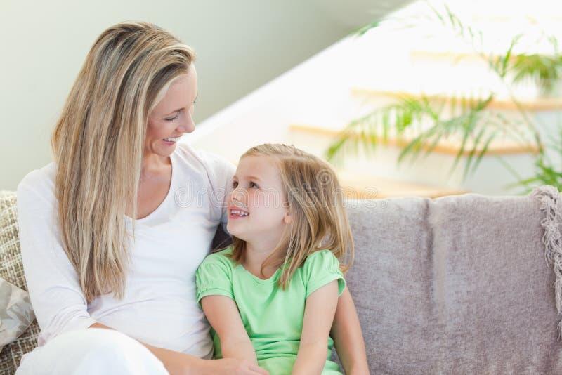 Moder och dotter som sitter på sofaen arkivbild
