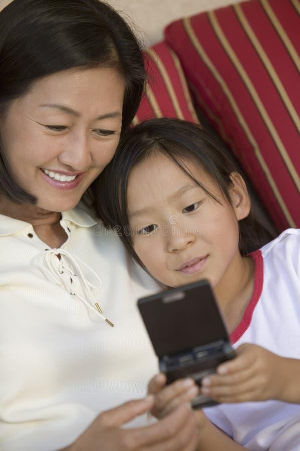 Moder och dotter som spelar den Handheld videospelet på soffan royaltyfri bild