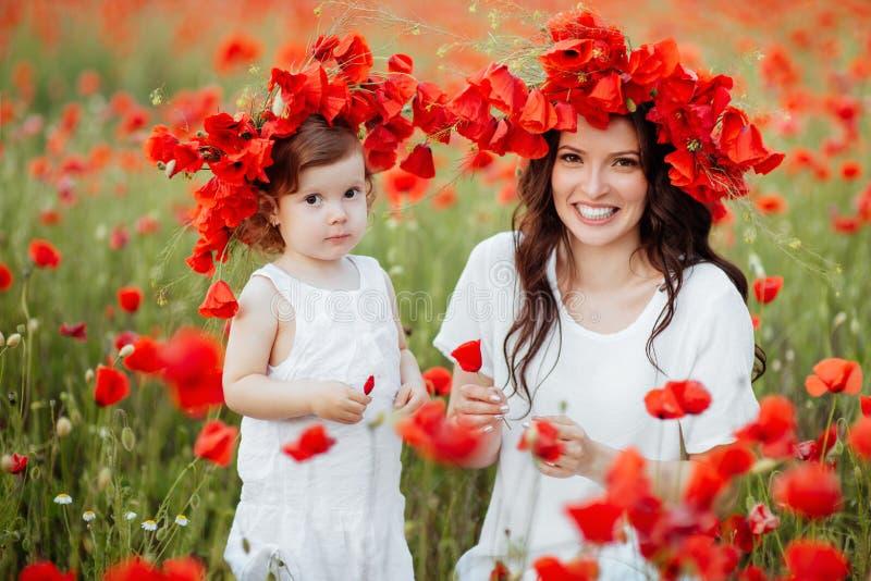 Moder och dotter som spelar i blommafält arkivbilder