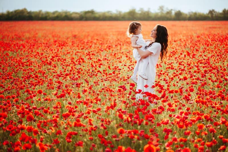 Moder och dotter som spelar i blommafält arkivfoton