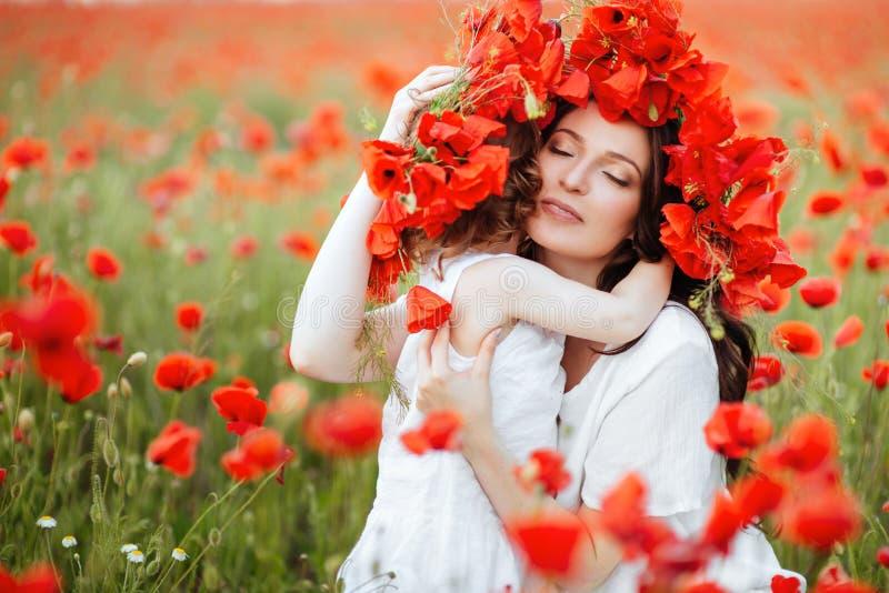 Moder och dotter som spelar i blommafält fotografering för bildbyråer