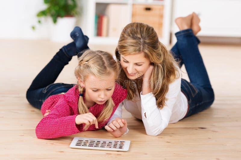 Moder och dotter som spelar med en minnestavla arkivbild