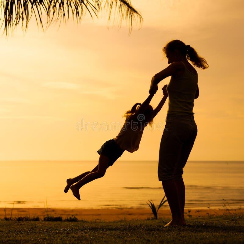 Moder och dotter som spelar på stranden royaltyfria foton