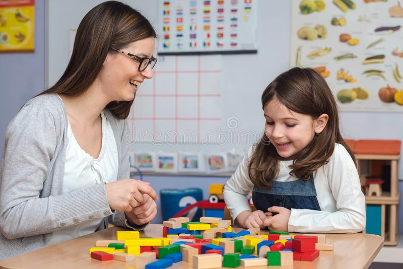 Moder och dotter som spelar samman med färgrika byggnadsleksakkvarter royaltyfri foto