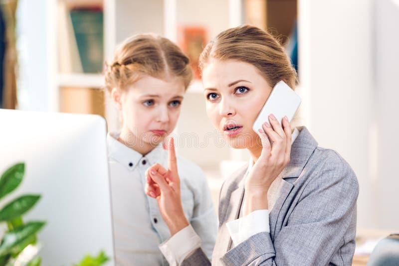 Moder och dotter som talar i affärskontor, affärskvinna som använder smartphonen arkivfoton