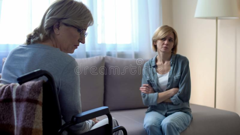 Moder och dotter som talar i sjukhuset, missförstånd, familjkonflikt royaltyfria foton