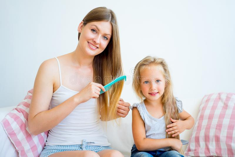 Moder och dotter som tar omsorg av hår arkivbild