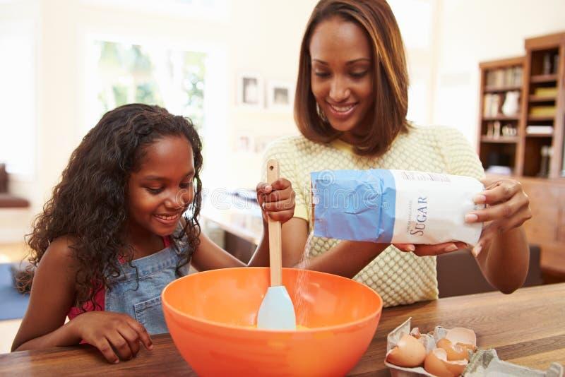 Moder och dotter som tillsammans hemma bakar arkivbild