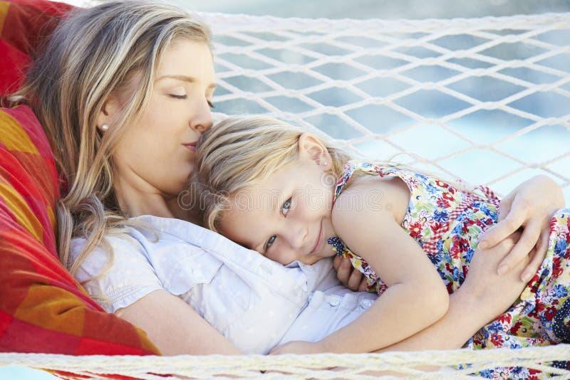 Moder och dotter som tillsammans kopplar av i trädgårds- hängmatta royaltyfri foto