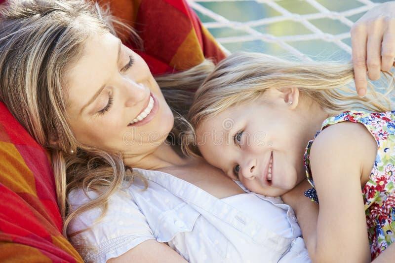 Moder och dotter som tillsammans kopplar av i trädgårds- hängmatta royaltyfria foton