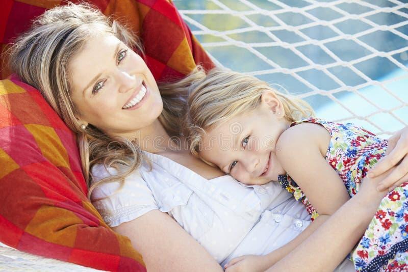 Moder och dotter som tillsammans kopplar av i trädgårds- hängmatta arkivbilder