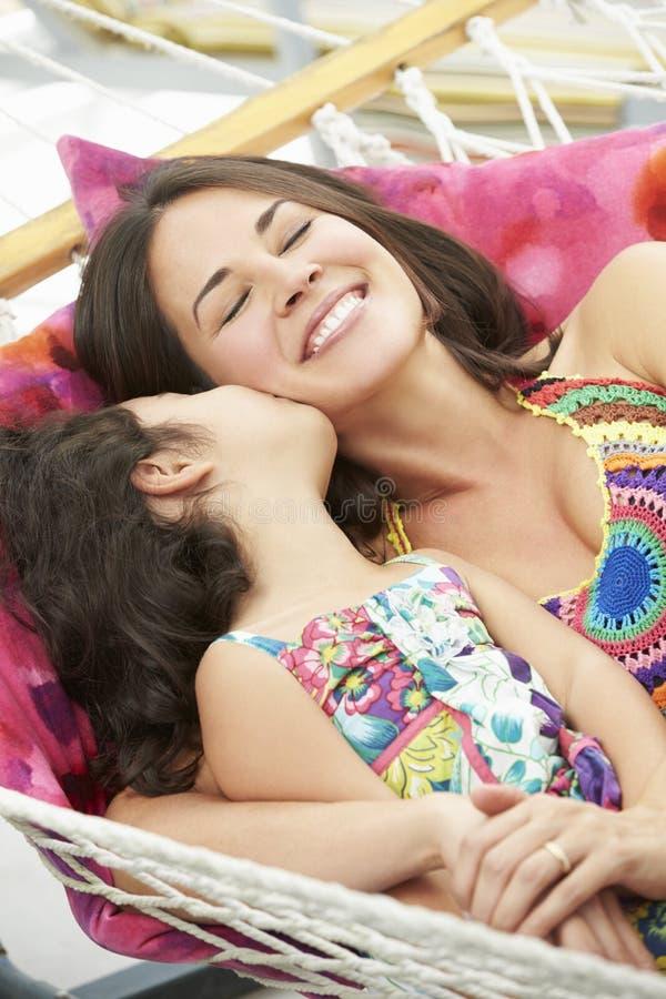 Moder och dotter som tillsammans kopplar av i trädgårds- hängmatta arkivfoton