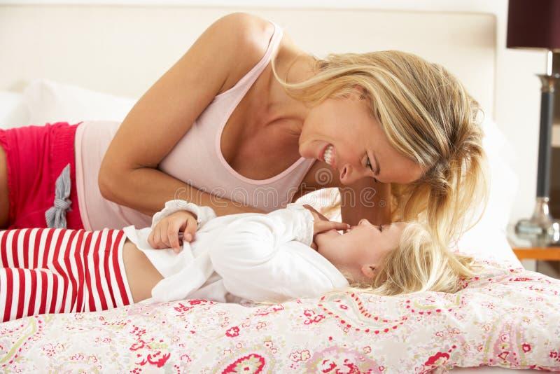 Moder och dotter som tillsammans kopplar av i underlag royaltyfri bild