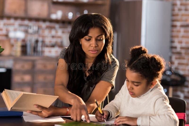 Moder och dotter som tillsammans lär på tabellen och gör läxa royaltyfri bild