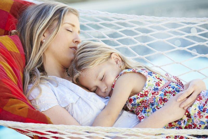 Moder och dotter som tillsammans sover i trädgårds- hängmatta royaltyfri fotografi