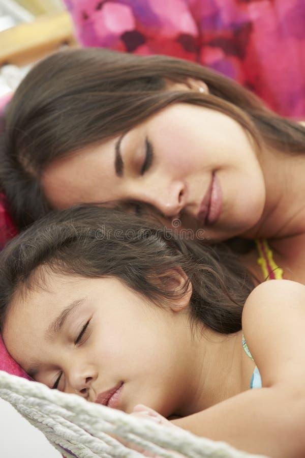 Moder och dotter som tillsammans sover i trädgårds- hängmatta royaltyfri bild