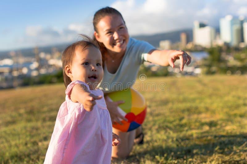 Moder och dotter som tillsammans spelar på parkera arkivfoton