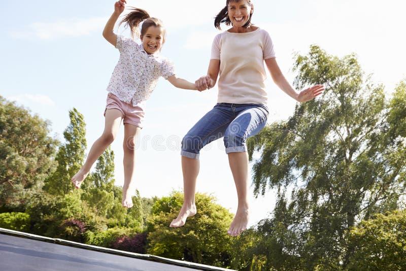Moder och dotter som tillsammans studsar på trampolinen arkivfoton