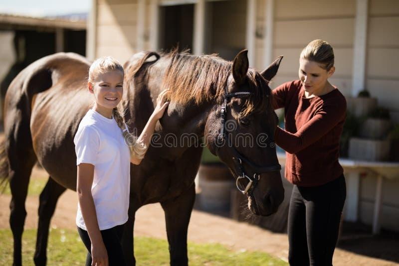 Moder och dotter som trycker på hästen arkivbild