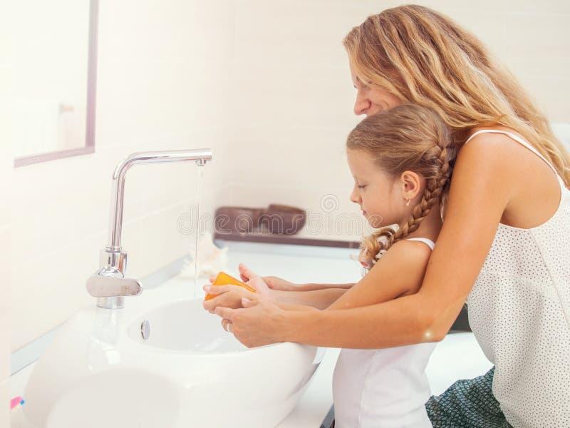 Moder och dotter som tv?ttar deras h?nder fotografering för bildbyråer