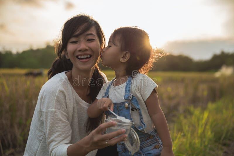 Moder och dotter som tycker om lek med den utomhus- bubblan royaltyfria foton