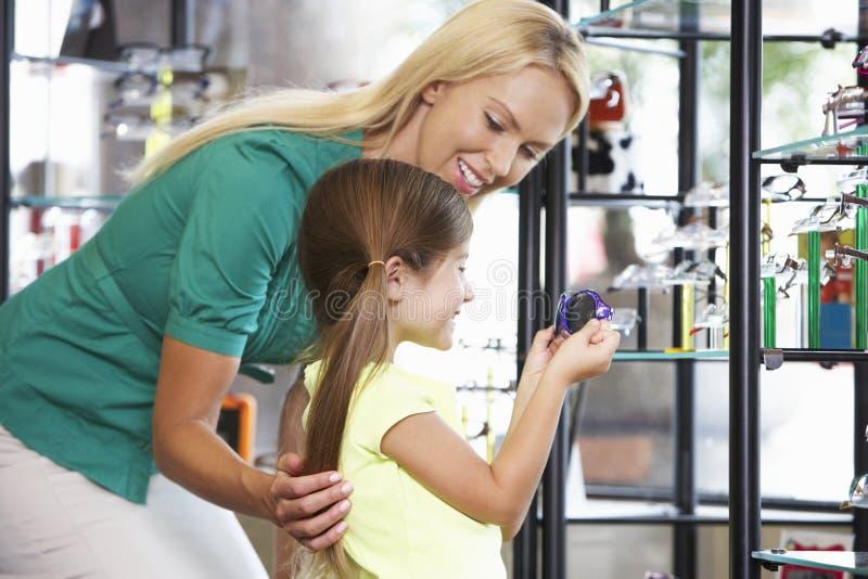 Moder och dotter som väljer exponeringsglas i optiker royaltyfria bilder