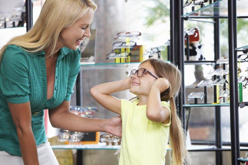 Moder och dotter som väljer exponeringsglas i optiker arkivbilder