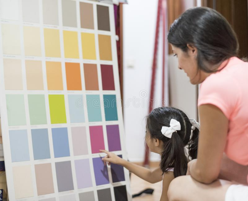Moder och dotter som väljer färger för målarfärgsovrum royaltyfria bilder