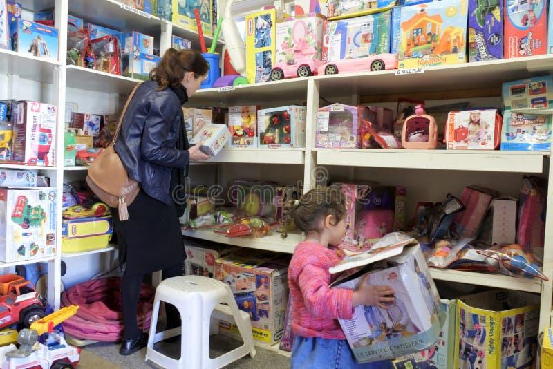 Moder och dotter som väljer leksaker i ett leksakarkiv royaltyfri bild