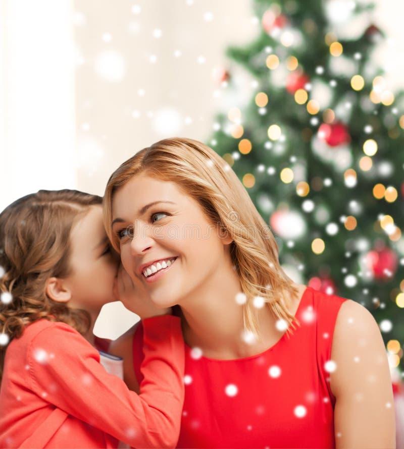 Moder och dotter som viskar skvaller royaltyfri bild