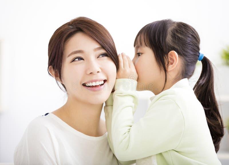 Moder och dotter som viskar skvaller royaltyfri fotografi