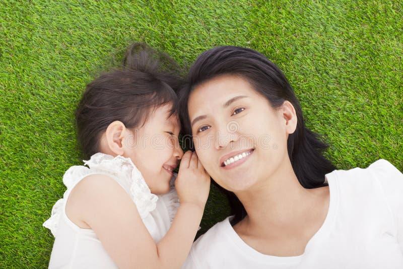 Moder och dotter som viskar skvaller på gräset royaltyfri foto