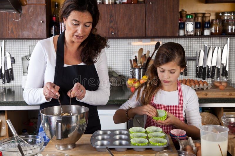 Moder- och dotterbakning hemma royaltyfri bild
