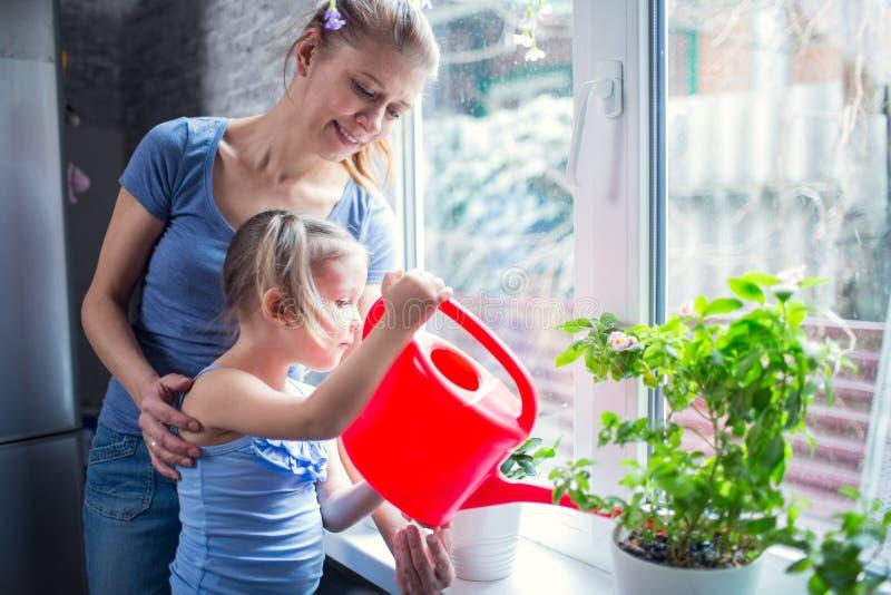 Moder- och dotterfamilj som bevattnar blommor på fönstret arkivbilder