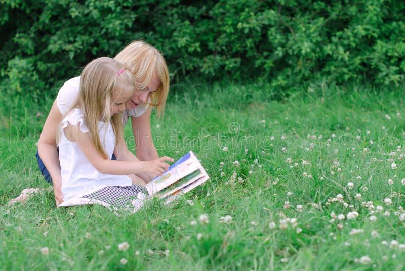 Moder- och dotterläsebok royaltyfria foton