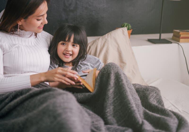 Moder- och dotterläsebok hemma i sovrummet fotografering för bildbyråer