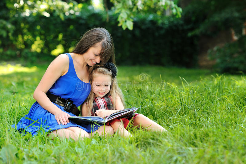 Moder- och dotterläsebok i en parkera arkivbilder