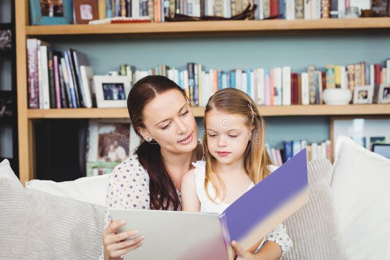 Moder- och dotterläsebok på soffan hemma arkivbilder