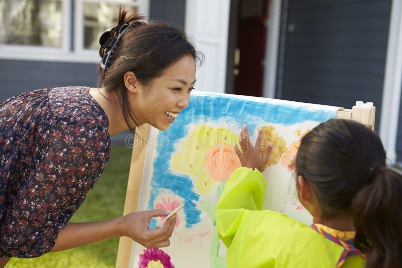 Moder- och dottermålningbild i trädgård tillsammans fotografering för bildbyråer