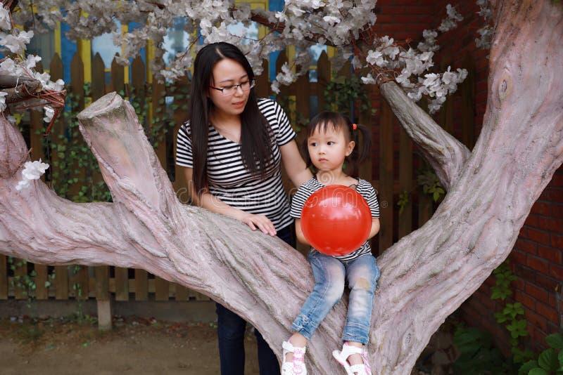 Moder- och dottermamman och behandla som ett barn lite flickan har gyckel in att parkera flickan sitter på en trädlek med röd bal arkivbilder