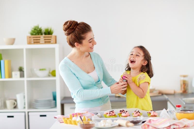 Moder- och dottermatlagningmuffin hemma arkivfoto