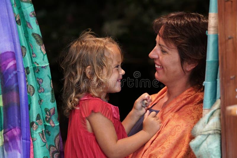 Moder- och dotterplayng och framställning av roliga framsidor i Oia royaltyfria bilder
