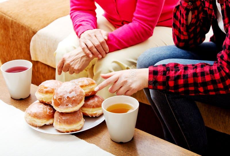 Moder- och dottersammanträde på soffan med donuts och te på tabellen fotografering för bildbyråer