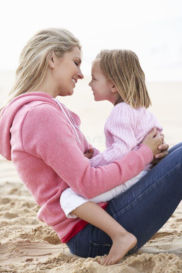 Moder- och dottersammanträde på stranden tillsammans arkivbilder