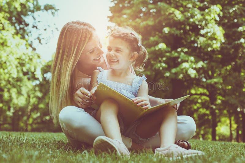 Moder- och dottersammanträde på toge för grönt gräs och läsebok arkivfoton