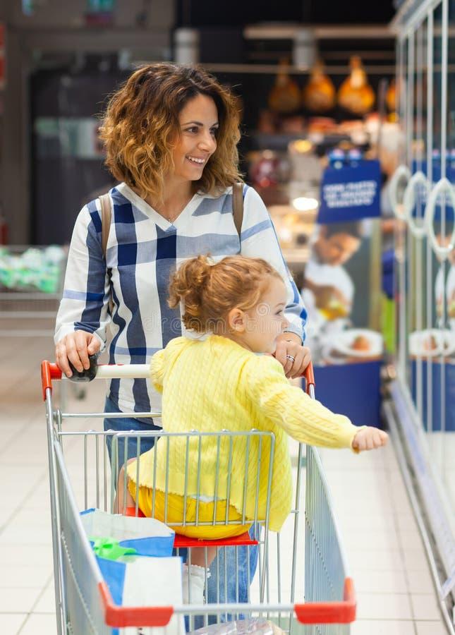 Moder- och dottershopping för livsmedel i supermarket arkivfoto