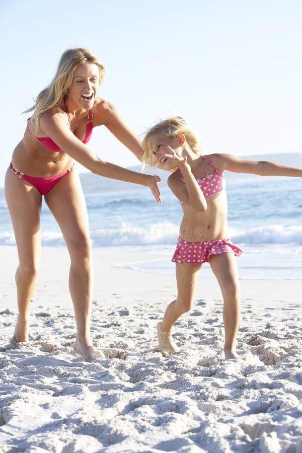 Moder- och dotterspring längs stranden som bär tillsammans baddräkten arkivfoton