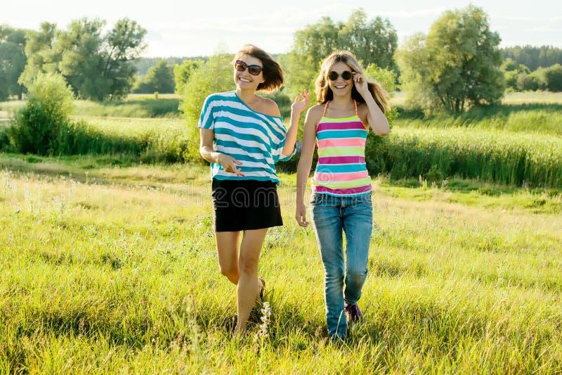 Moder- och dottertonåringen går i natur på en solig dag för sommar royaltyfri fotografi
