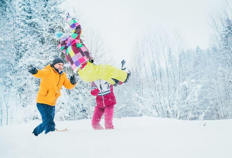 Moder- och faderfamilj som bedrar i snöskog, genom att kasta deras lilla daugher till snödrivan royaltyfria bilder