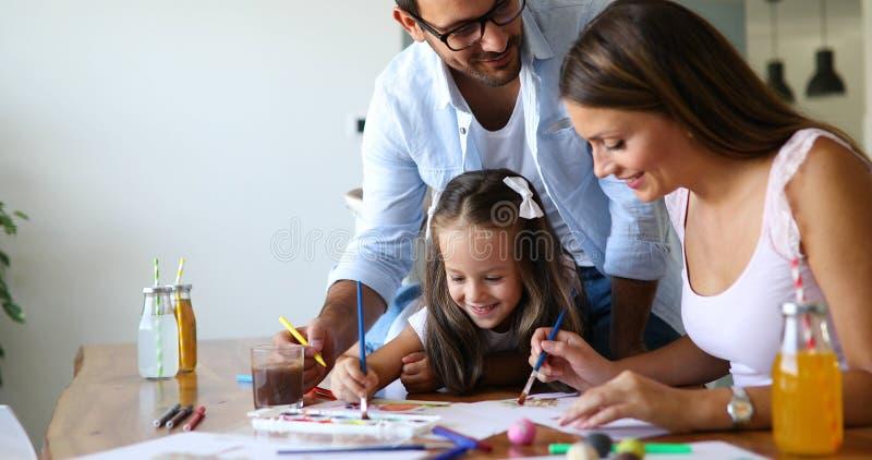 Moder- och faderteckning samman med deras barn royaltyfria foton